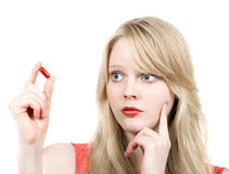 Young blond girl afraid with medicine pill Stock Photo