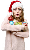 Young blond girl as santa`s hat with Christmas balls. Stock Images