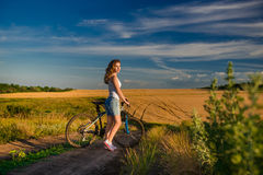 Young blond girl on the background of the rural landscape Royalty Free Stock Image