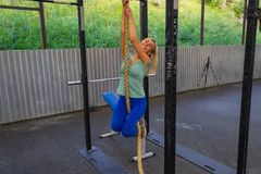 Young blond girl in blue leggings and green t-shirt smiling climbing up the rope in the gym among the horizontal bars against stock images