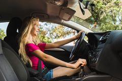 Young blond girl driver inside a car royalty free stock photo