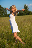 Young blond girl enjoying the freedom. Young blond girl in white dress enjoying the freedom Stock Images
