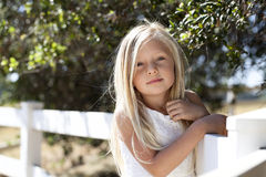 Young Blond Girl on Fence. A young girl with long blond hair leaning against white fence with leaves of oak trees blurred in background Royalty Free Stock Images