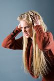 Young blond girl furiously scratches Royalty Free Stock Photography