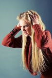 Young blond girl furiously scratches Stock Image