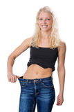 Young blond girl had a weight loss. A young, natural blond girl, holding out the waist of her jeans, isolated on white background Stock Photos