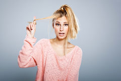 Young Blond Girl with Hair Problems. Ona Grey Background Royalty Free Stock Photos