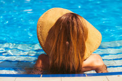 Young blond girl has a rest at the pool. Rear view. Summertime Stock Photo