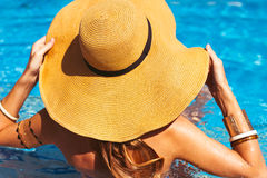 Young blond girl has a rest at the pool. Rear view. Summertime Royalty Free Stock Photo