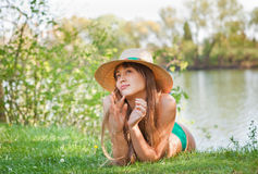 Young blond girl with a hat lying on the grass Stock Photography