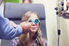 Eye exam. A young blond girl having an eye examination at an optometrist's clinic Stock Images