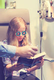 Eye exam. A young blond girl having an eye examination at an optometrist's clinic Royalty Free Stock Photography