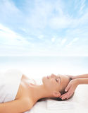 A young blond girl on a head massage procedure Stock Photography