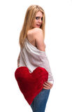Young blond girl with a heart pillow Royalty Free Stock Images