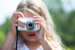 Young blond girl holding digital camera and photographing Royalty Free Stock Photos