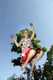 Young blond girl jumps against blue sky Royalty Free Stock Photo