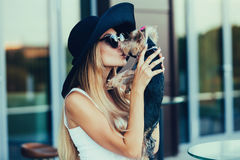 Young blond girl kissing small dog. Beautiful young blond girl kissing small dog on journey stock photography