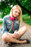 Young blond girl listening music Stock Photos