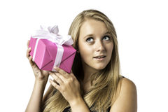 Young blond girl listens to a gift Stock Photography