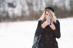 Young blond girl looking at phone outside in snow. Young blond alternative girl in black clothes looking at phone Stock Photography
