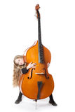 Young blond girl looks from behind double bass in studio Stock Photos