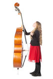 Young blond girl looks up to double bass in studio Royalty Free Stock Photography