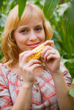 Young blond girl with maize Royalty Free Stock Photography
