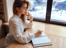 Young blond girl making notes in a notebook. While sitting at the table Royalty Free Stock Photos