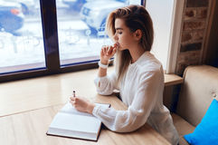 Young blond girl making notes in a notebook. While sitting at the table Royalty Free Stock Image