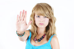 Young blond girl making STOP gesture. Young blond teenager girl with sad or angry face raising her hand to say NO or STOP, strong concept against drugs, violence Stock Images