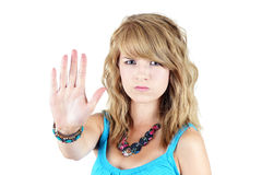 Young blond girl making STOP or NO gesture. Young blond teenager girl with sad or angry face raising her hand to say NO or STOP, strong concept against drugs Royalty Free Stock Images
