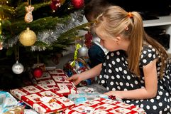 Girl opening Christmas present under Christmas tree Royalty Free Stock Photography