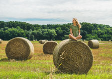 Young blond girl sitting on haystack and smiling, Hungary Royalty Free Stock Photos