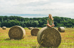 Young blond girl sitting on haystack and smiling, Hungary Stock Photos