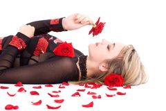 Young blond girl smelling red rose Royalty Free Stock Photo
