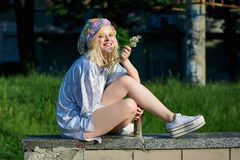 Young blond girl in sparkling hat with dandelions Royalty Free Stock Images