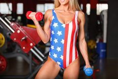 Young girl pump biceps with multi-colored dumbbells. Inside the gym. Young blond girl with a sporty physique in a sporty tights swings biceps with multi-colored Royalty Free Stock Images