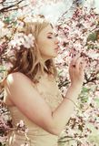 Young blond girl in spring flowers garden Royalty Free Stock Photography