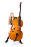 Young blond girl stands behind double bass in studio Stock Photo