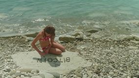 Young blonde girl in bathing suit sits alone on a rocky beach and makes up the word Bitcoin stock video footage