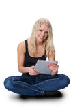 Young blond girl with a tablet. A young pretty girl with blond hair, sitting with a tablet, isolated on white background Royalty Free Stock Photos