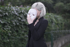 Young blond girl taking off a mask. Pretending to be someone else concept. outdoors. Young blond girl taking off a mask. Pretending to be someone else concept Royalty Free Stock Photography