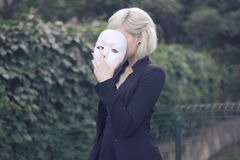 Young blond girl taking off a mask. Pretending to be someone else concept. outdoors. Stock Photography