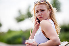 Young blond girl talking on cell phone. Facial expressions Royalty Free Stock Photos