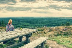 Young blond girl trekker resting at wooden table royalty free stock photography