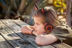 Young Blond Girl Wearing Earphone With Cat Ears on Top Sitting C. A young, blond girl sits with her chin on her hands at a picnic table in the desert with late stock image