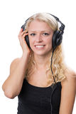Young blond girl wearing headphones. Young blond girl with a fantastic smile, wearing headphones, isolated on white background Royalty Free Stock Photography