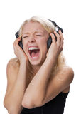 Young blond girl wearing headphones, screaming. A young natural blond girl wearing headphones while screaming, isolated on white background Stock Photography