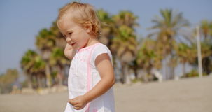 Young Blond Girl in White Dress on Tropical Beach. Close Up of Young Blond Girl Wearing White Dress and Standing on Tropical Beach with Palm Trees  Smiling and stock footage