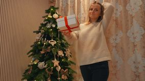 The girl gives his girlfriend a New Year gift under the tree. A young blond girl in a white woolen sweater gives a New Year`s gift to her best friend near a stock video
